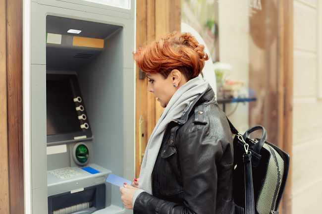 iStock-530505942_woman with red hair at bank ATM_resized.png