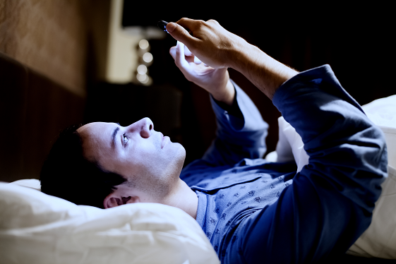 iStock-531769925_resized_man using phone in bed.png